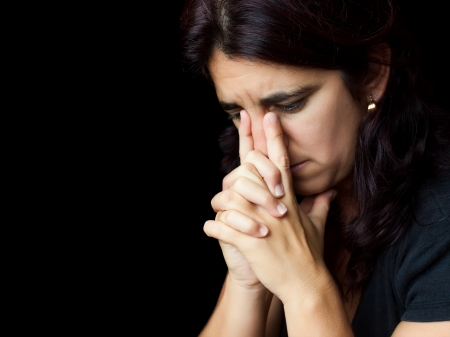 Portrait of a sad and stressed hispanic woman with a thoughtful expression isolated on black Stock Photo - 14429208