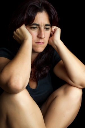 Depressed and worried hispanic woman with a thoughtful expression sitting on the floor isolated on black photo