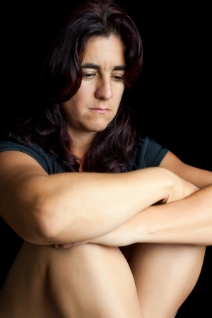 Sad and worried hispanic woman sitting on the floor with a thoughtful expression isolated on black photo