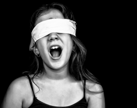 Black and white image of a small girl screaming and blindfolded with a handkerchief isolated on black with space for text photo