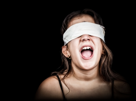 detainee: Small girl screaming with her eyes blindfolded with a handkerchief isolated on black with space for text Stock Photo
