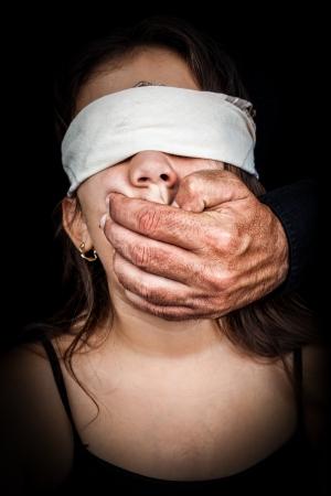 maltrato infantil: Pequeña niña ciega con un pañuelo con una mano de hombre adulto cubriendo su boca sobre un fondo negro