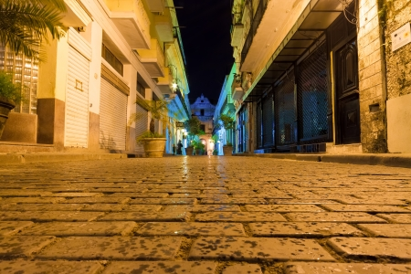city alley: Narrow street sidelined by typical buildings illuminated at night in Old Havana Stock Photo