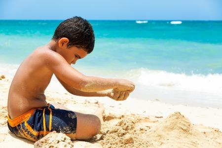 children sandcastle: Hispanic boy building a sand castle on a beautiful tropical beach