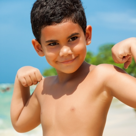 nios hispanos: Ni�o hispano que muestra sus m�sculos en una hermosa playa tropical Foto de archivo