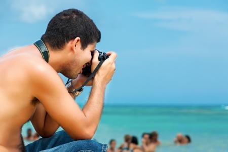 amateur: Fotógrafo amateur hispano tomando fotos en la playa