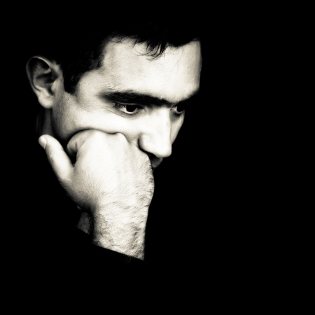 proble: Black and white  dramatic close-up  of a man thinking with a fist on his chin emerging from a black background