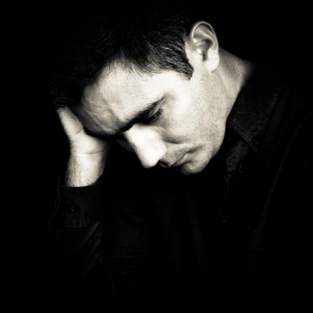 homme triste: Portrait noir et blanc d'un homme inquiet et d�prim� isol� sur noir