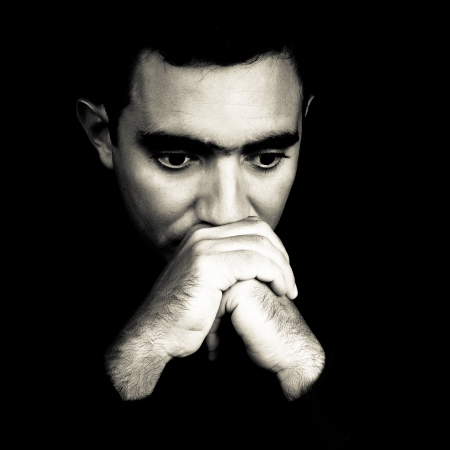 homme inquiet: Dramatique visage noir et blanc d'un homme inquiet, jeune sortant d'un fond noir Banque d'images