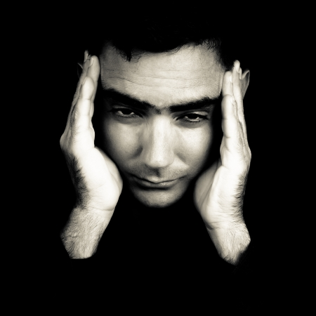 Dramatic black and white portrait of a man suffering a strong headache or depression pressing his forehead with his hands isolated on black photo
