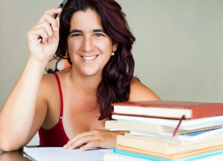 Beautiful adult hispanic woman studying  with a stack of books on her desk and smiling at the camera photo