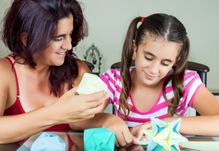 Young  mother and her daughter making paper models or origami photo