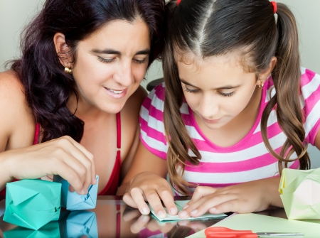 Young mother and her daughter making paper models or origami Stock Photo - 14745383