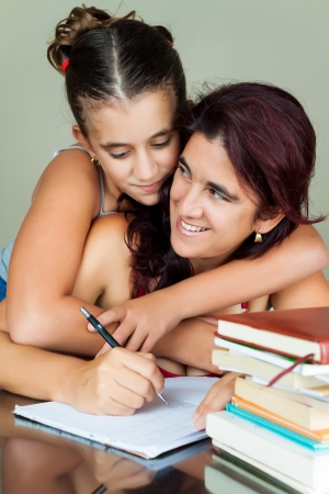 Young hispanic woman working or studying at home while her daughter hugs her from behind Stock Photo - 14745385