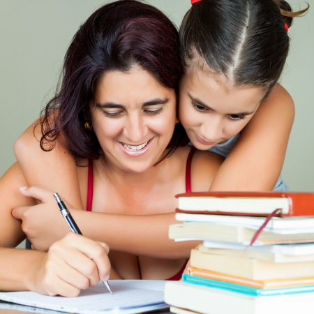 Young hispanic woman working or studying at home while her daughter hugs her from behind photo