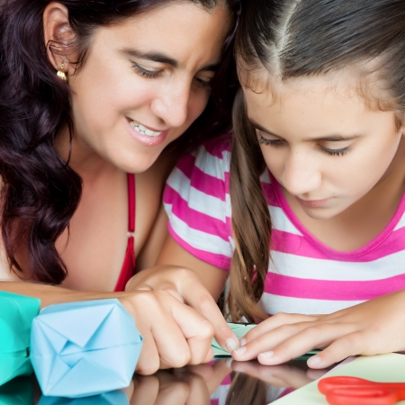 Close-up of an hispanic mother and daughter making origami at home