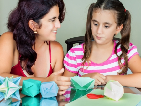 Hipanic mother and daughter making origami at home photo