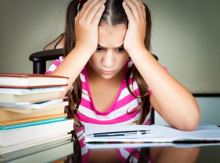 Angry and tired schoolgirl studying with a pile of books on her desk photo