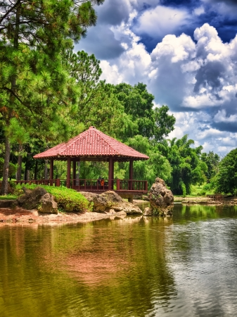 Red roofed pavilion above a lake on a beautiful ornamental japanese garden