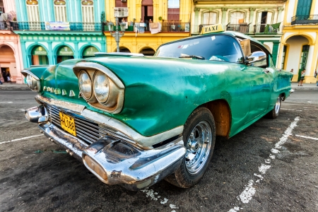 taxi famous building: Vintage car in a colorful neighborhood in Havana Editorial