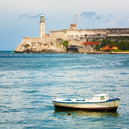 The Castle of El Morro, a worldwide known  landmark of Havana with a small fishing boat on the foreground photo