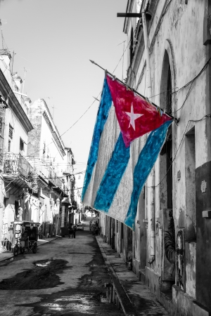 Black and white street scene in Old Havana with a colorful cuban flag photo
