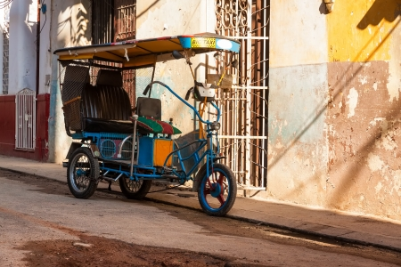 Bycicle used as taxi in a shabby neighborhood in Old Havana photo