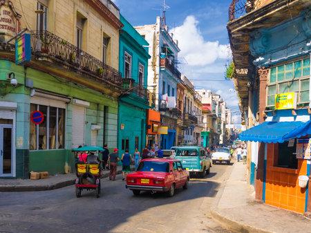 La gente y los coches viejos en una céntrica calle de La Habana
