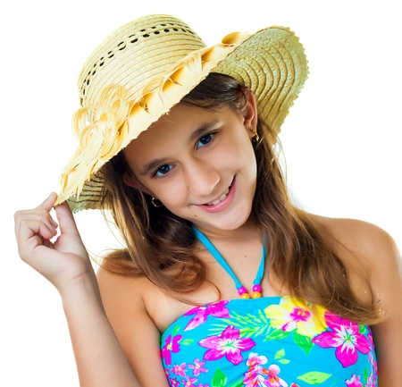 preteens beach: Beautiful hispanic girl wearing a colorful swimsuit and a straw hat smiling isolated on white