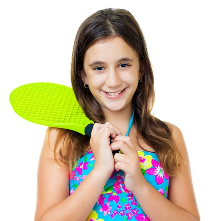 preteens beach: Lovely hispanic girl wearing a colorful swimsuit and holding a yellow racquet isolated on white Stock Photo