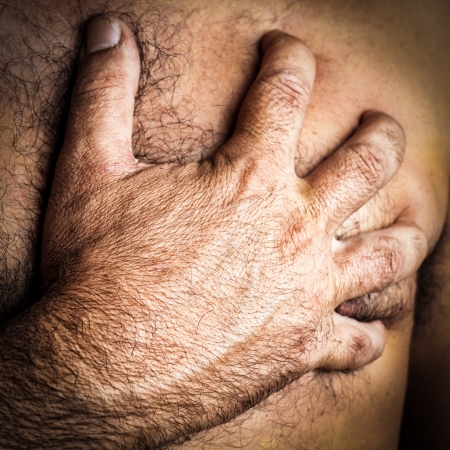 Close up of a hand grabbing the chest of a man who is suffering a heart attack Stock Photo - 15511015