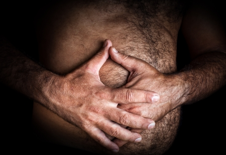 colon cancer: Close up image of a shirtless man suffering from severe abdominal pain Stock Photo