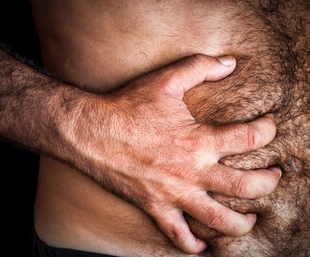 Close up image of a shirtless man suffering from severe abdominal pain Stock Photo - 15368111