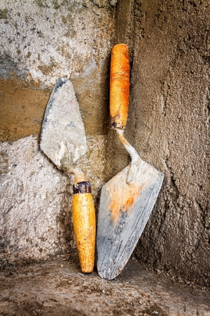 Dirty trowels leaning on a rough concrete wall photo