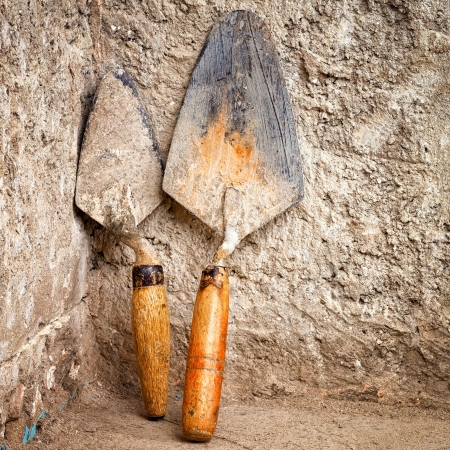 Metallic trowels leaning on a rough concrete wall photo