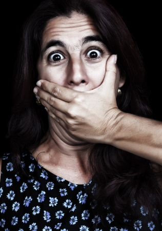 Grunge image of a frightened woman covering her mouth useful to ilustrate gender violence or discrimination  on a black background  photo