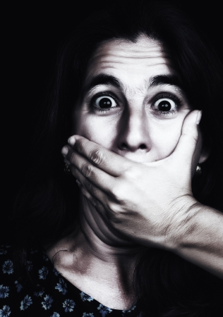 human gender: Grunge image of a frightened woman covering her mouth useful to ilustrate gender violence or discrimination  on a black background  Stock Photo