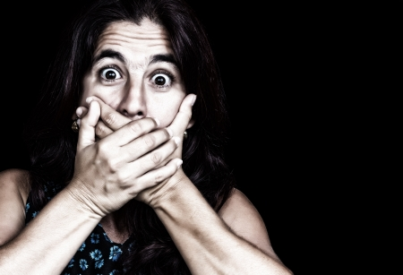 Grunge image of a frightened woman covering her mouth useful to ilustrate gender violence or discrimination  on a black background  Stock Photo - 15833443