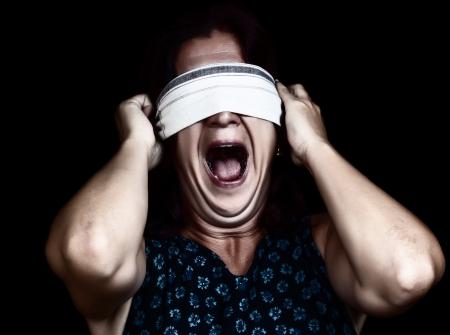 ojos vendados: Dramática imagen de una mujer asustada gritando y tapándose los ojos para no ver aislado en negro sirve para ilustrar la delincuencia, la violencia de género o la discriminación