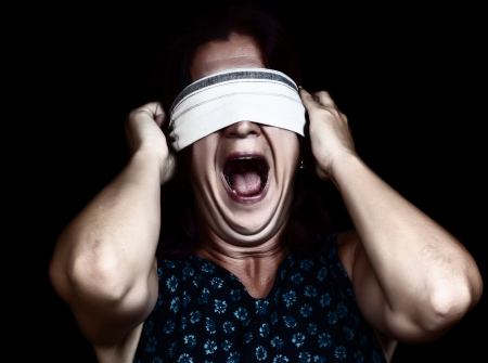 Dramatic image of a frightened woman screaming   and covering her eyes to avoid seeing isolated on black  useful to illustrate crime, gender violence or discrimination  photo