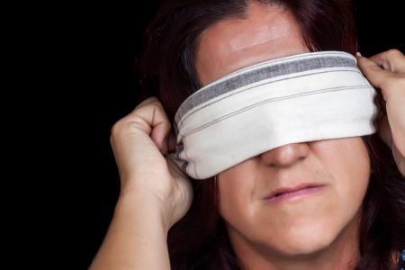 ojos vendados: Retrato de una mujer seria que cubre sus ojos con un pañuelo para no ver aislado en negro (útil para ilustrar la violencia de género o la discriminación)