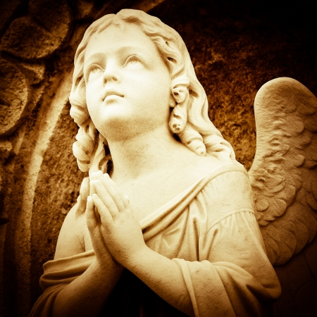 Beautiful vintage image of a praying angel in sepia shades photo