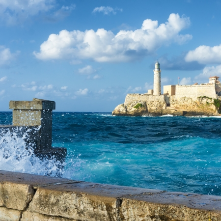 spanish architecture: The famous castle of El Morro in Havana with a stormy weather and big waves crashing against the wall