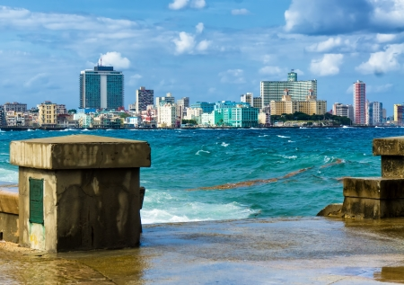 The skyline of Havana with a turbulent sea and El Malecon in the foreground photo
