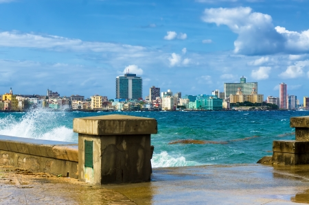 The skyline of Havana with a turbulent sea and waves crashing against the seaside wall photo