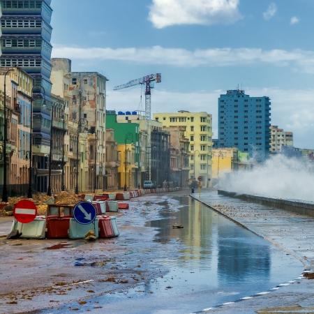 Havana during a hurricane with big waves crashing against the seaside wall and debris on the street