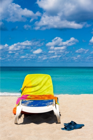 Plastic bed covered by colorful towels and a pair of flip flops on the beautiful beach of Varadero in Cuba photo
