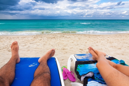 View of the feet of a couple resting on plastic beds on a tropical beach in Cuba photo