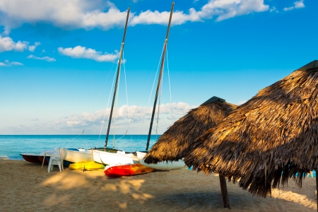 Sailing boats and thatched umbrellas lit by sunrise at the beach of Varadero in Cuba photo
