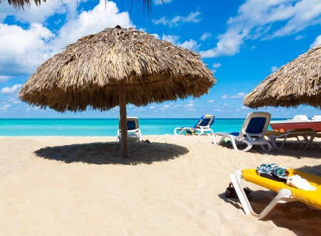 thatched: Thatched umbrellas and beach beds on the cuban beach of Varadero